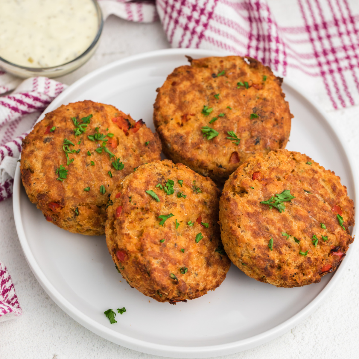 Air Fryer Salmon Cakes on a white plate with dipping sauce on the side.