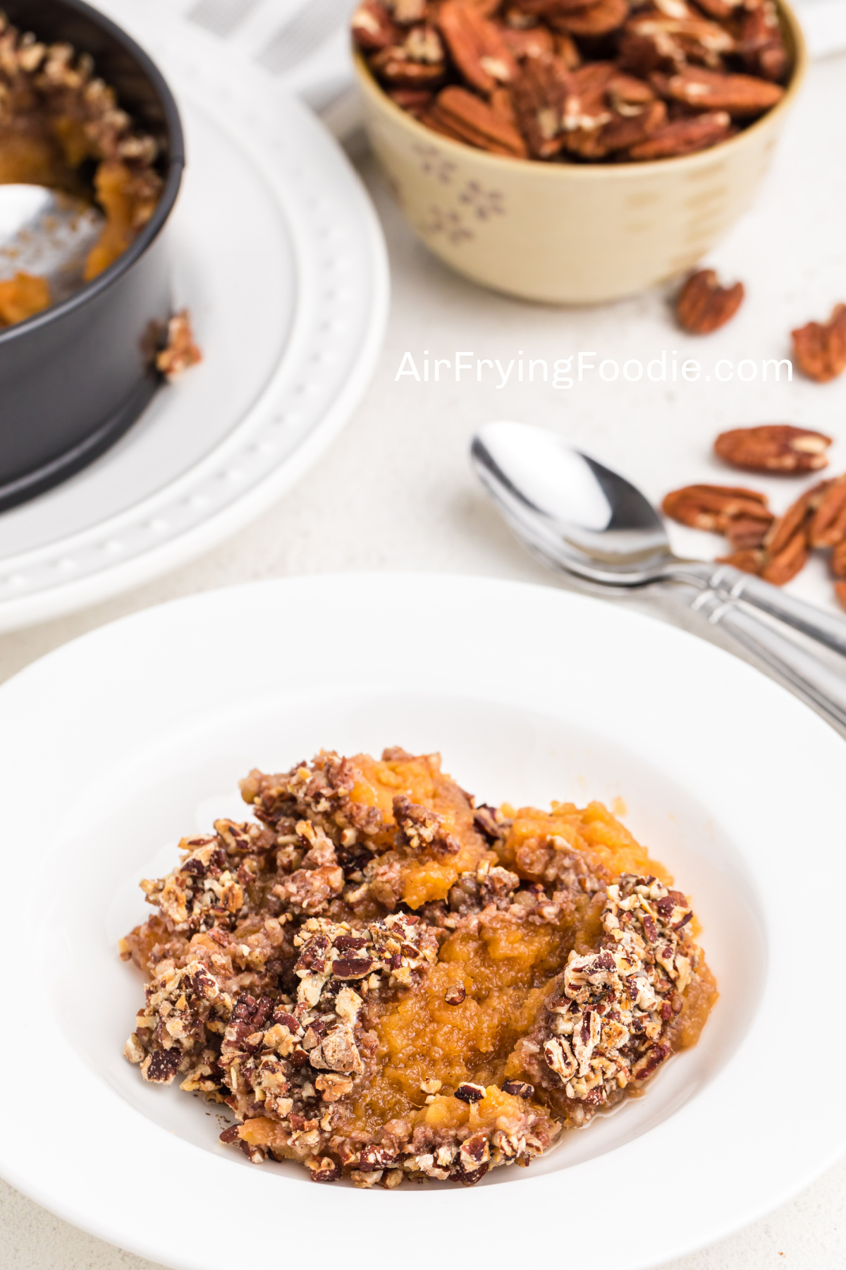 Sweet Potato Casserole topped with pecans in a white dish ready to eat.