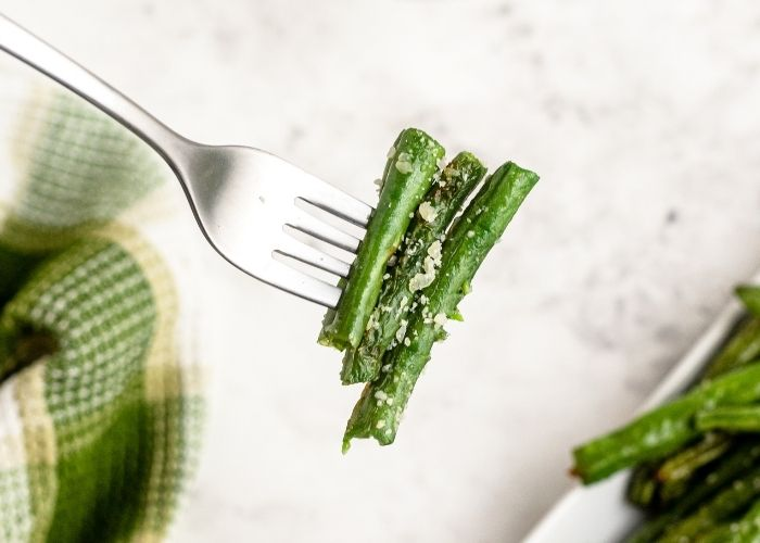 Green beans cooked and juicy on a fork after being sprinkled with grated parmesan cheese.