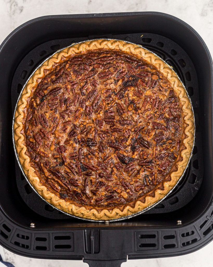 Pecan pie in an air fryer basket after being cooked.