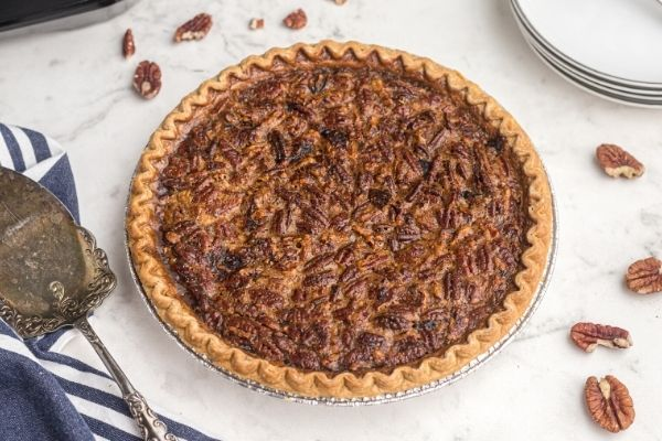Golden pecan pie on a white marble table with scattered pecans.