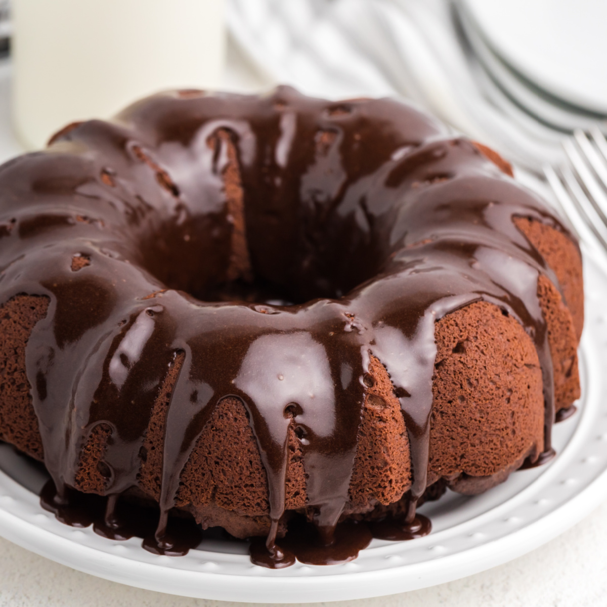 Chocolate Bundt Cake on a white plate and topped with chocolate frosting.