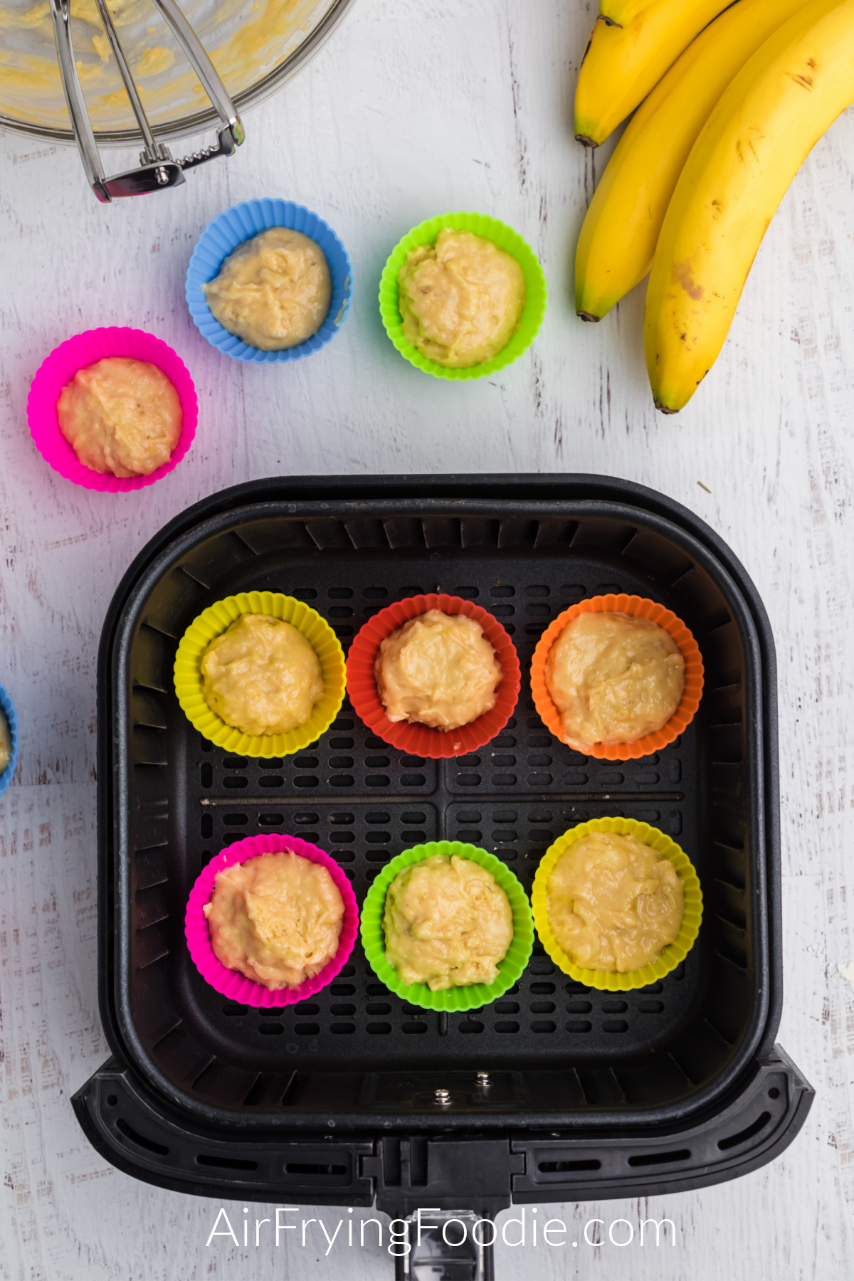 Air Fryer basket with silicone molds with banana muffin batter ready to cook.