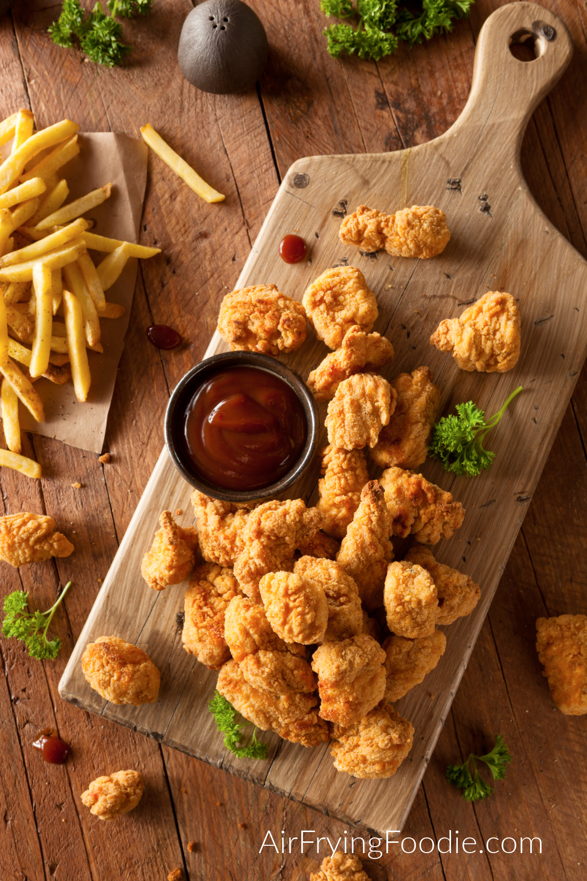 Crispy Air Fryer Chicken Bites on a cutting board served with ketchup.