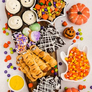 Overhead of board filled with brownies, cupcakes, mummy dogs, donut holes and candy scattered around the table.