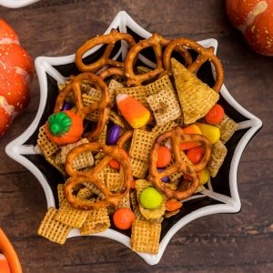 Spider web shaped black bowl filled with chex mix, Halloween candies, and pretzels.