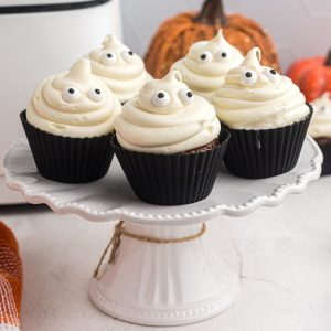 Chocolate cupcakes on a white cake stand with ghost vanilla frosting and candy eyes.