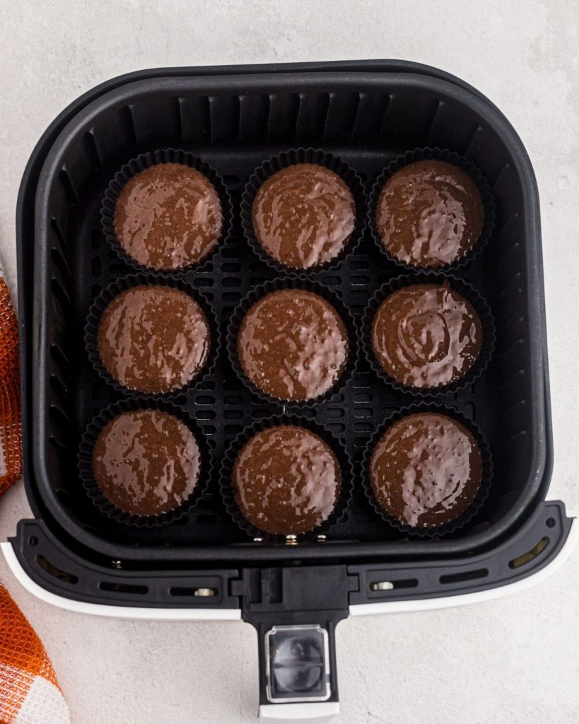 Uncooked cupcakes in the air fryer basket.