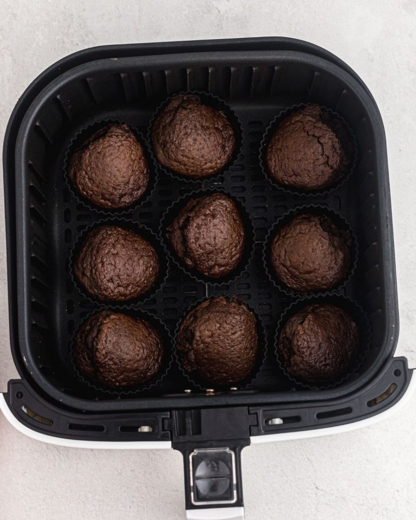 Cooked chocolate cupcakes in an air fryer basket.