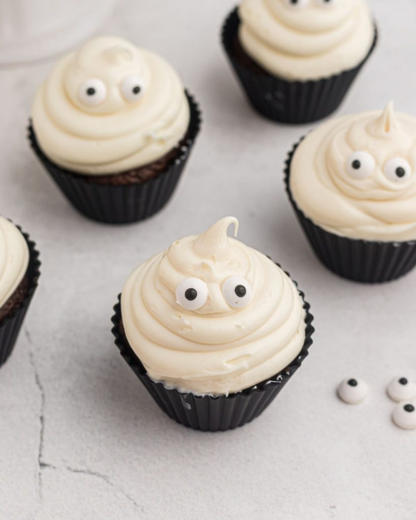 Ghost cupcakes as they are being made with candy eyes on the table.