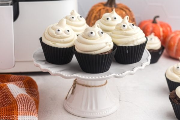 Ghost cupcakes on a white stand in front of an air fryer with pumpkins in the background.