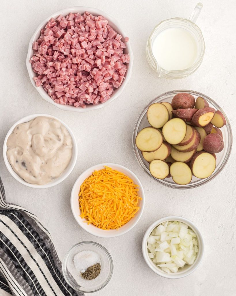 Ingredients needed for casserole measured in white bowls on a white table.