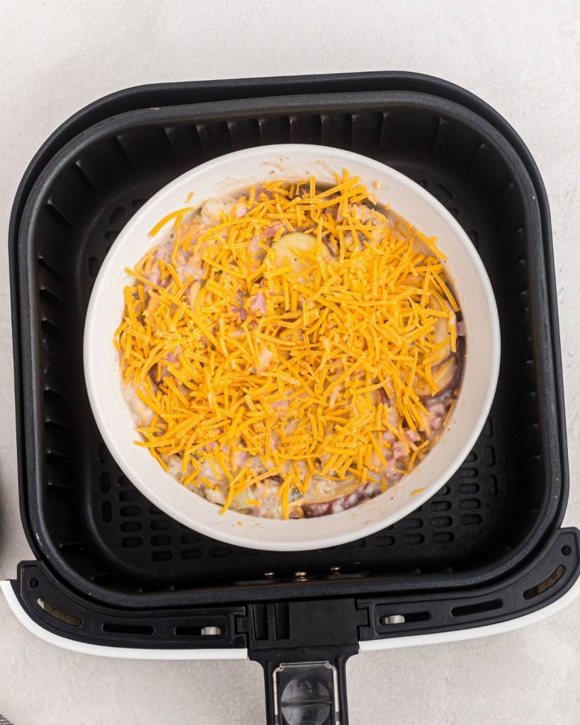 Bowl of ham and potatoes mixed with cheese and onions before being cooked, in the air fryer basket.