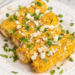 Close up of air fryer Mexican street corn on a white plate ready to serve.