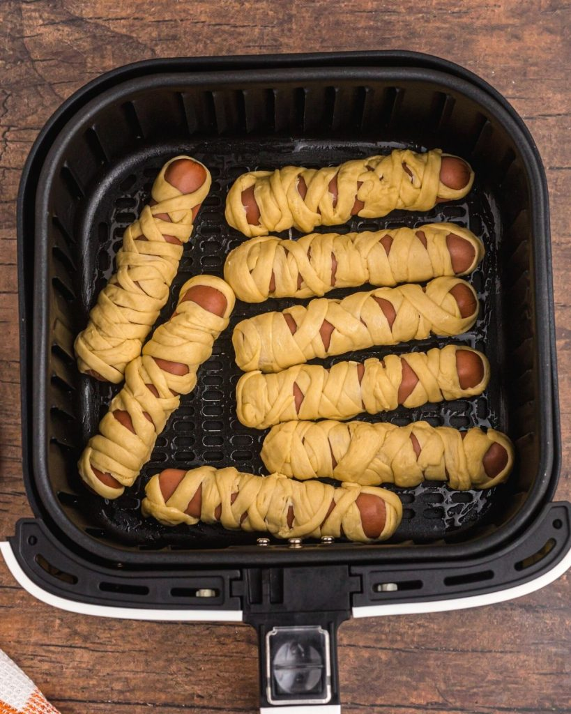 Hot dogs wrapped in crescent roll strips to look like mummies in the air fryer basket before being cooked.