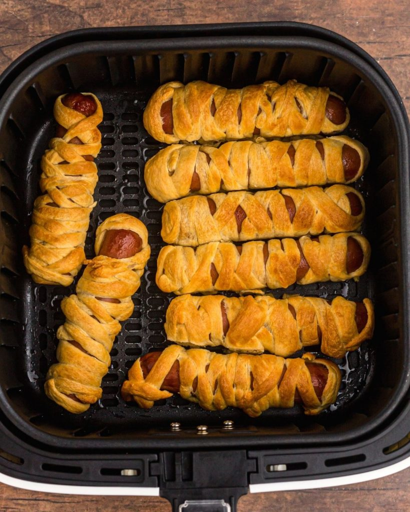 Air fryer basket full of mummy dogs after being cooked in the air fryer.