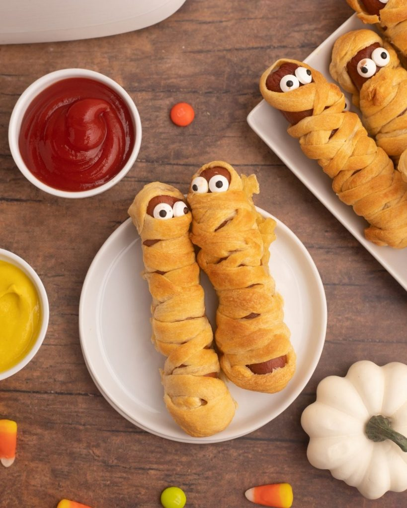 Golden hot dog mummies on a white plate with mustard and ketchup and candies scattered around the table.