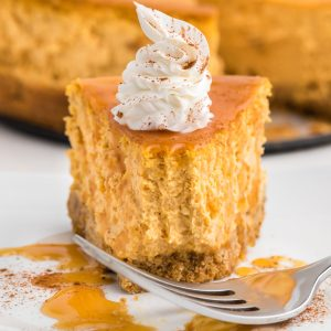 Air Fryer pumpkin cheesecake slice on a white plate with a bite missing.