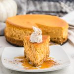 Slice of air fryer pumpkin cheesecake on a white plate ready to eat.