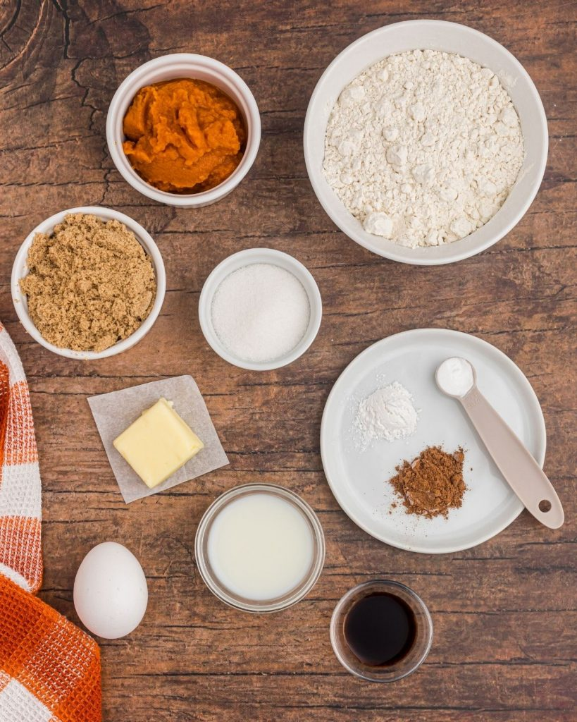 Ingredients needed to make pumpkin spice donut holes, laid out on a wooden table with an orange and white baking cloth..