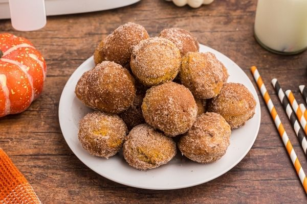 Golden sugar and cinnamon coated donut holes on a white plate on a wooden table