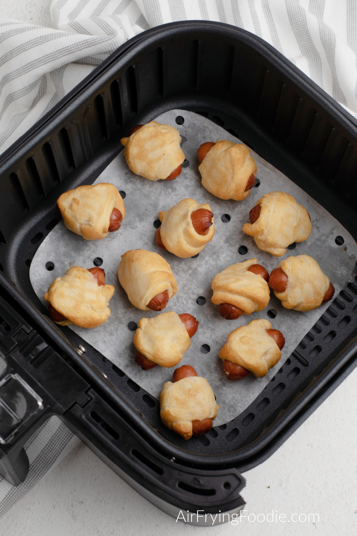 Batch of air fried pigs in a blanket in the basket of the air fryer.